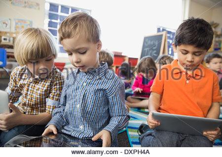 Schoolboys using digital tablet in elementary classroom - Stock Photo