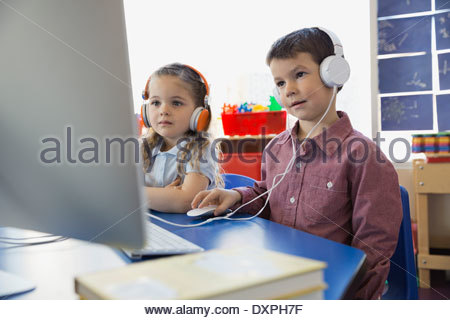 Students wearing headphones using computer in school - Stock Photo