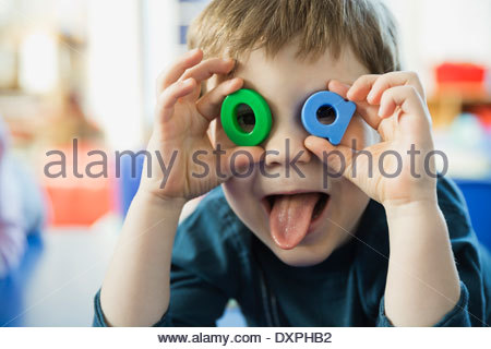 Playful boy making faces with letters - Stock Photo