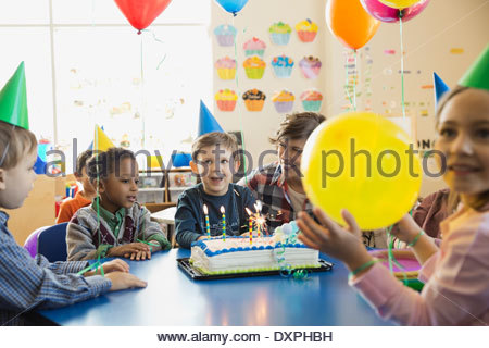 Teacher and children celebrating birthday in school - Stock Photo