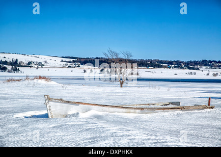 Old wooden rowboat buried in snow in rural Prince Edward Island. - Stock Photo