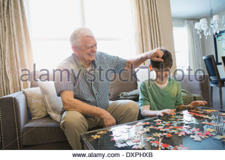 Playful grandfather and grandson solving puzzle at home - Stock Photo