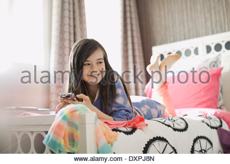 Smiling girl with smart phone lying on bed - Stock Photo