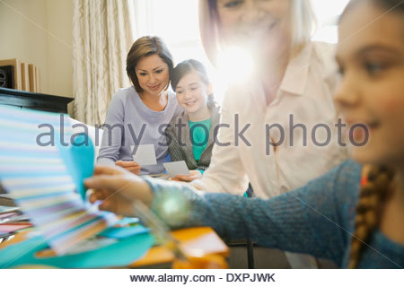 Smiling mother and daughter looking at photos while scrapbooking - Stock Photo