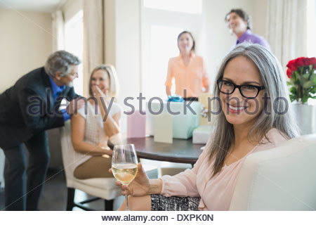 Portrait of smiling woman holding wineglass at birthday party - Stock Photo