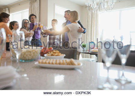 Family and friends toasting wineglasses at party - Stock Photo