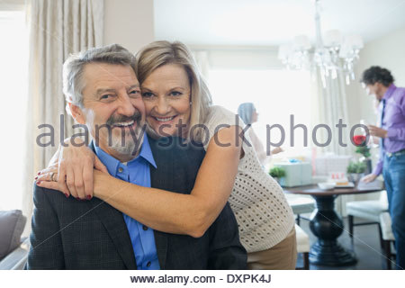 Portrait of cheerful woman embracing man at party - Stock Photo