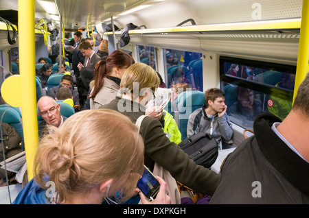 Rush hour commuters on board crowded First Capital Connect train, London, England, UK - Stock Photo