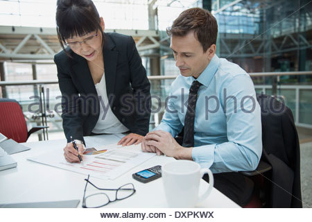 Business people reviewing data in meeting - Stock Photo