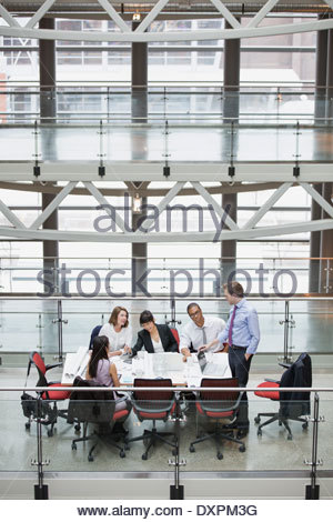 Business people meeting at conference table on atrium balcony - Stock Photo