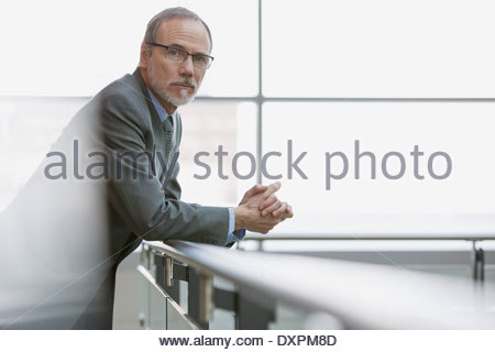 Portrait of confident businessman leaning on railing - Stock Photo