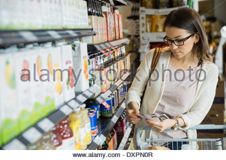 Woman shopping with coupons in market - Stock Photo