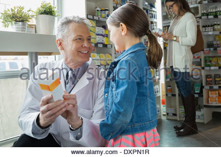 Pharmacist consulting girl in market - Stock Photo