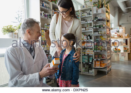 Pharmacist consulting mother and daughter in market - Stock Photo