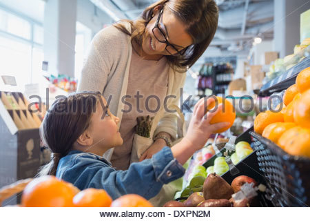 Mother and daughter shopping for produce in market - Stock Photo