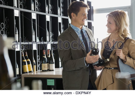 Couple comparing bottles in wine store - Stock Photo