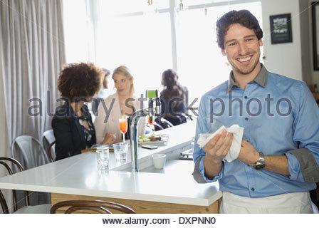 Portrait of bartender drying wine glass in bar - Stock Photo