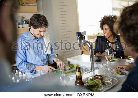 Customers watching bartender slice fruit behind bar - Stock Photo