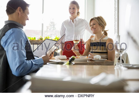 Waitress taking couples order at table in bistro - Stock Photo