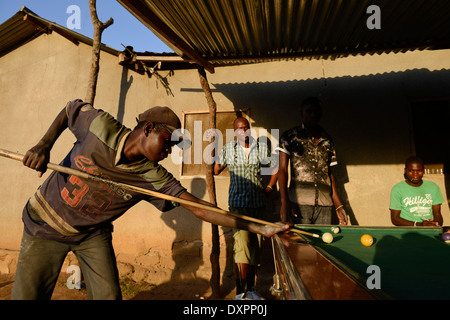 TANZANIA Geita, artisanal gold mining in Mgusu, where about 4000 people live and work, young miner play billiards - Stock Photo