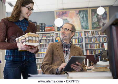 Bookstore owner with digital tablet talking to woman - Stock Photo