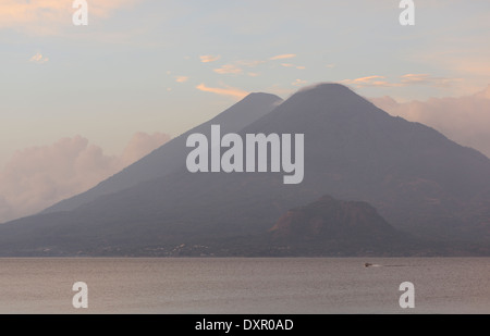 Early morning view across Lake Atitlan from Panajachel. A motor boat passes in front of Volcan Toliman, 3153m, - Stock Photo
