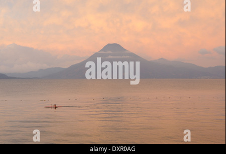 Early morning view across Lake Atitlan from Panajachel. A canoeist paddles in front of  Volcan San Pedro 3020m.. - Stock Photo