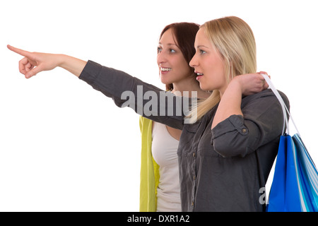 A young woman with shopping bags showing her friend something, isolated on a white background - Stock Photo