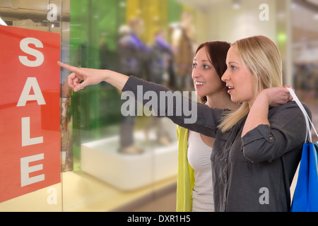 A young woman with shopping bags showing her friend something in a window - Stock Photo