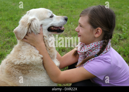 Little girl and her dog on a meadow in nature - Stock Photo