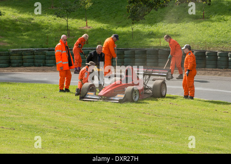 Marshals clearing the track after an incident at Prescott hill climb in Gloucestershire, England - Stock Photo