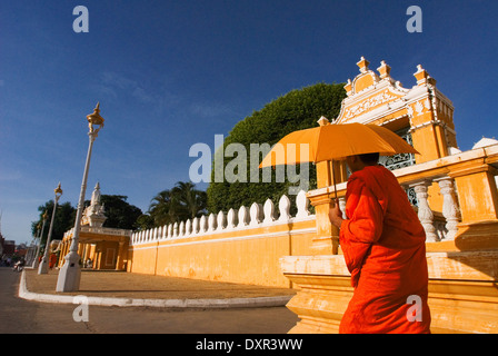 Monks walk outside the Royal Palace. Phnom Penh. Gleaming in gold, the Royal Palace is one of Phnom Penh?s most - Stock Photo