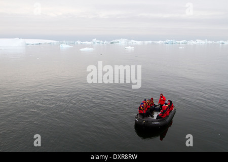Antarctica cruise ship tourism among the landscape of Antarctic iceberg, icebergs, glacier, and ice with tourists in zodiac.