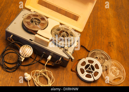 An antique toy tape recorder from the 1950s or 60s with lapel microphone, earphone and reels of magnetic recording - Stock Photo