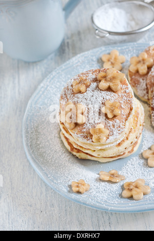 Homemade pancakes with sugar powder and flower-shaped banana slices on light blue plate. Selective focus. - Stock Photo