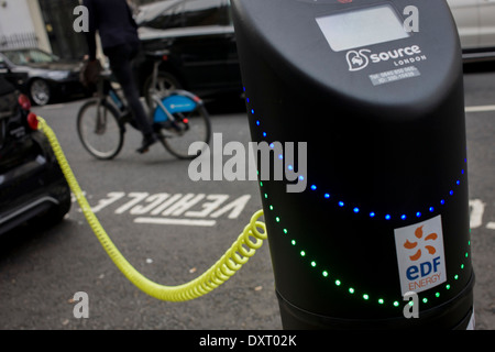 Cyclist passes a parked Smart car recharges electric power at an EDF charging point in central London. - Stock Photo