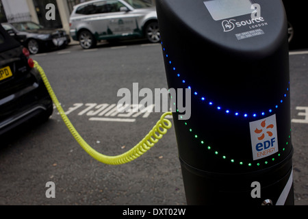A parked Smart car recharges electric power at an EDF charging point in central London. - Stock Photo