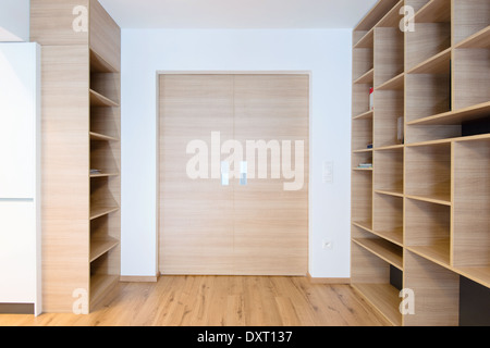 empty bookshelves and closed door in empty apartment - Stock Photo