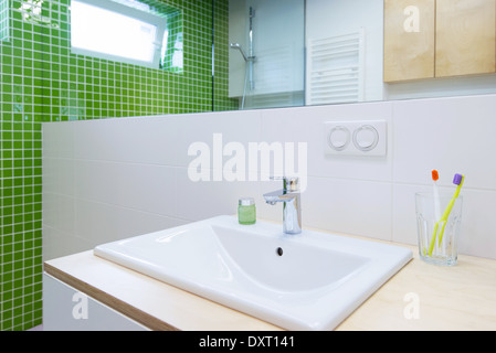 wash basin with faucet in green bathroom - Stock Photo