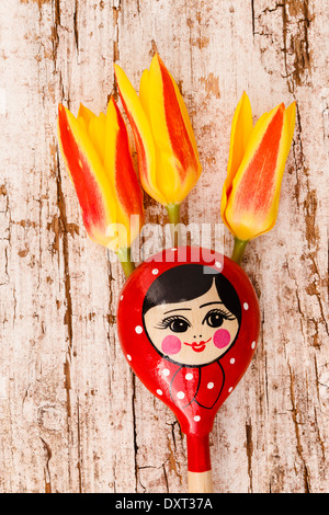 Russian wooden spoons matryoshka with tulips - Stock Photo