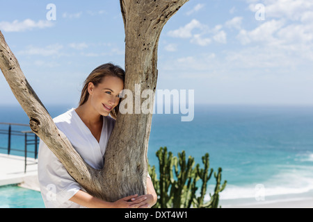 Smiling woman in bathrobe hugging tree in front of ocean - Stock Photo