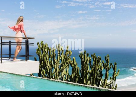 Woman standing on poolside balcony overlooking ocean - Stock Photo