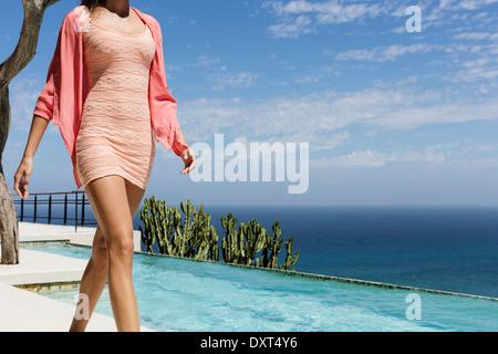 Woman walking along swimming pool overlooking ocean - Stock Photo