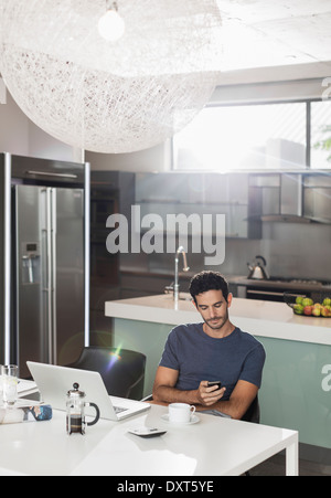 Man texting with cell phone at kitchen table - Stock Photo