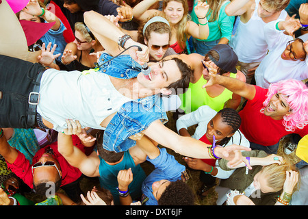 Performer with microphone crowd surfing at music festival - Stock Photo