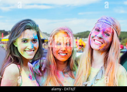 Portrait of smiling women covered in chalk dye at music festival - Stock Photo