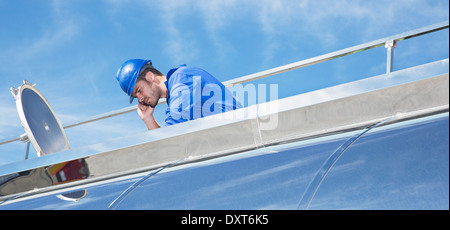 Worker on platform above stainless steel milk tanker - Stock Photo
