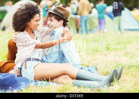 Couple hugging in grass outside tents at music festival - Stock Photo