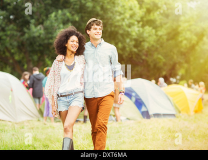 Couple walking outside tents at music festival - Stock Photo