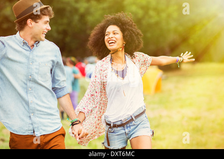 Happy couple in field outside tents at music festival - Stock Photo
